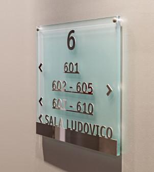 Schild aus Glas mit Relief-Buchstaben